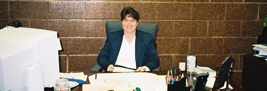Staff member poses at her desk