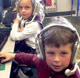 Two students wearing headphones as they use computers