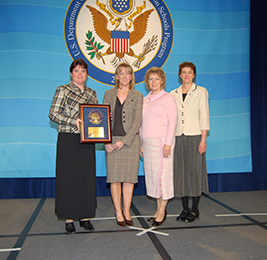 Staff members pose with Blue Ribbon Plaque