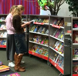 Staff members look at books at the Scholastic Book Fair