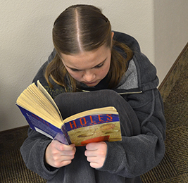 Female student reads the book Holes as she sits on the floor