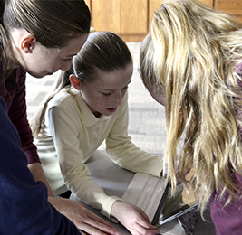 Three female students work on a project together