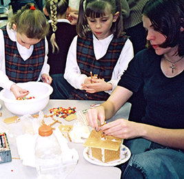 Staff member makes a gingerbread house with two students
