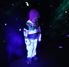 Student dressed as Buzz Lightyear poses in glow in the dark room