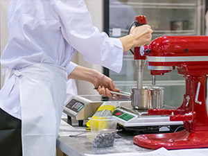 chef with red kitchenaid and weight scales