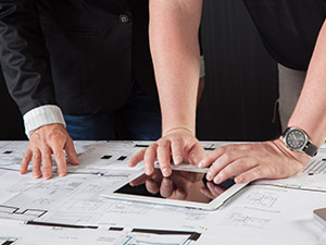 two people reading blueprints