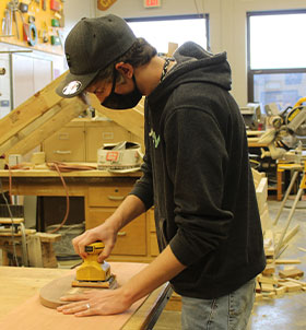 Student making wooden football