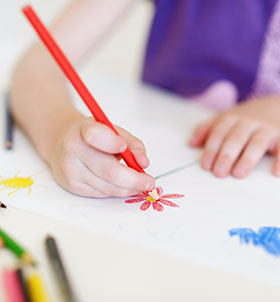 Child drawing flowers at a table