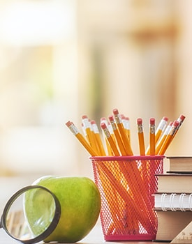 Pencils, an apple and a magnifying glass sit on a desk next to stacked books