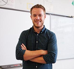 Smiling male staff member posing in front of a white board