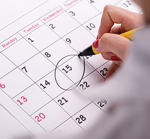 Person circling the 15th date on a calendar with a pen