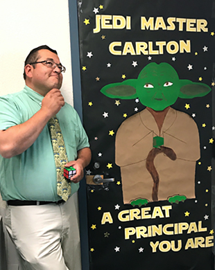Principal Carlton posing in front of a door decoration with Yoda and the words Jedi Master Carlton, A Great Principal You Are on it