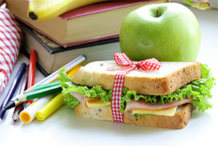 A sandwich, a banana, an apple, stacked books, markers and pencils