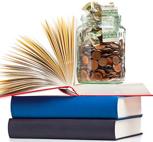 Jar full of dollars and coins sitting on top of stacked books