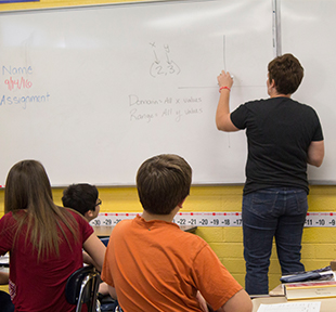 Teacher writing on a white board in front of students at their desks