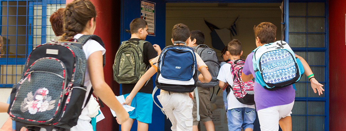 Students wearing backpacks running through school doors