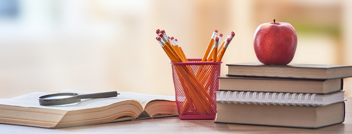 An open book with a magnifying glass on top of it, pencils, and an apple sitting on top of a stack of books