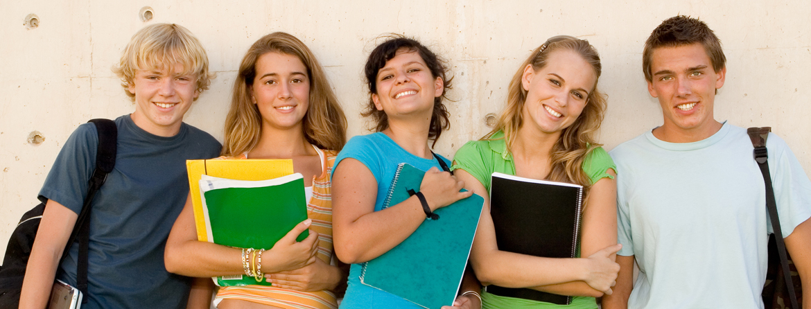 Five students holding notebooks and smiling
