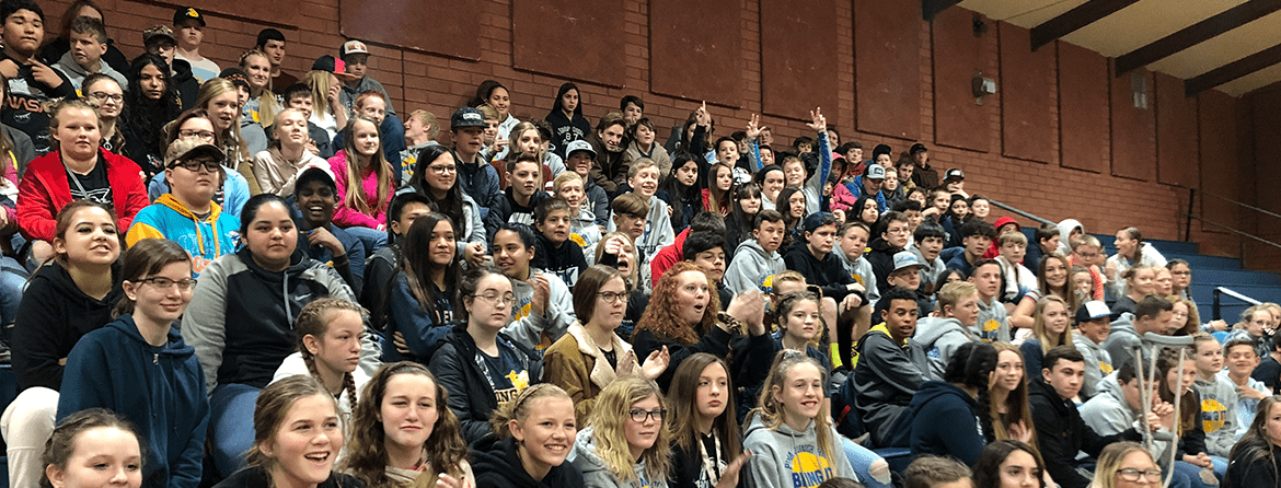 Large group of students sitting together and posing on bleachers in a gym
