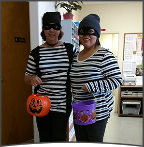 Two female staff members pose wearing bandit costumes as they hold Halloween baskets