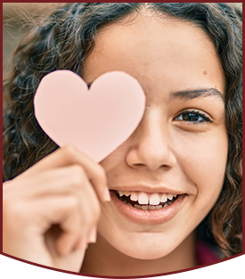 Hispanic teenager girl smiling and holding a paper heart