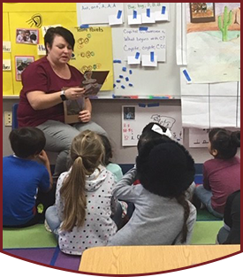 Teacher reading to students as they sit on the classroom floor