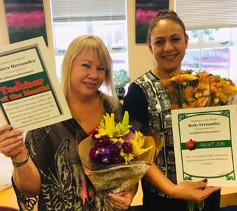 Barbara Hernandez and Betty Fernandez holding flowers and certificates