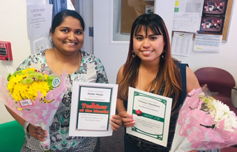 Mable Shaju and Yumara Martinez holding flowers and certificates