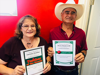 Teacher of the Month Christine Bastidas and Employee of the Month Alvaro Monteverde holding their awards
