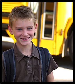 student in front of a school bus