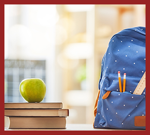 stacked books with green apple on top, blue backpack with pencil and ruler in pocket