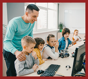 happy young teacher helping his students at computers