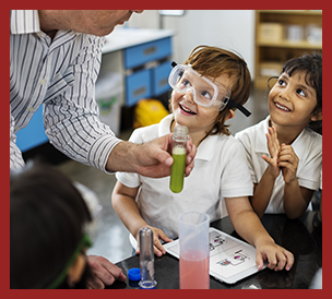 teacher showing students with safely goggles science experiment