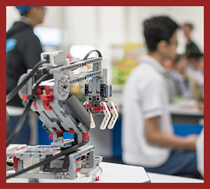 robotic lab with students in background and a robot in foreground