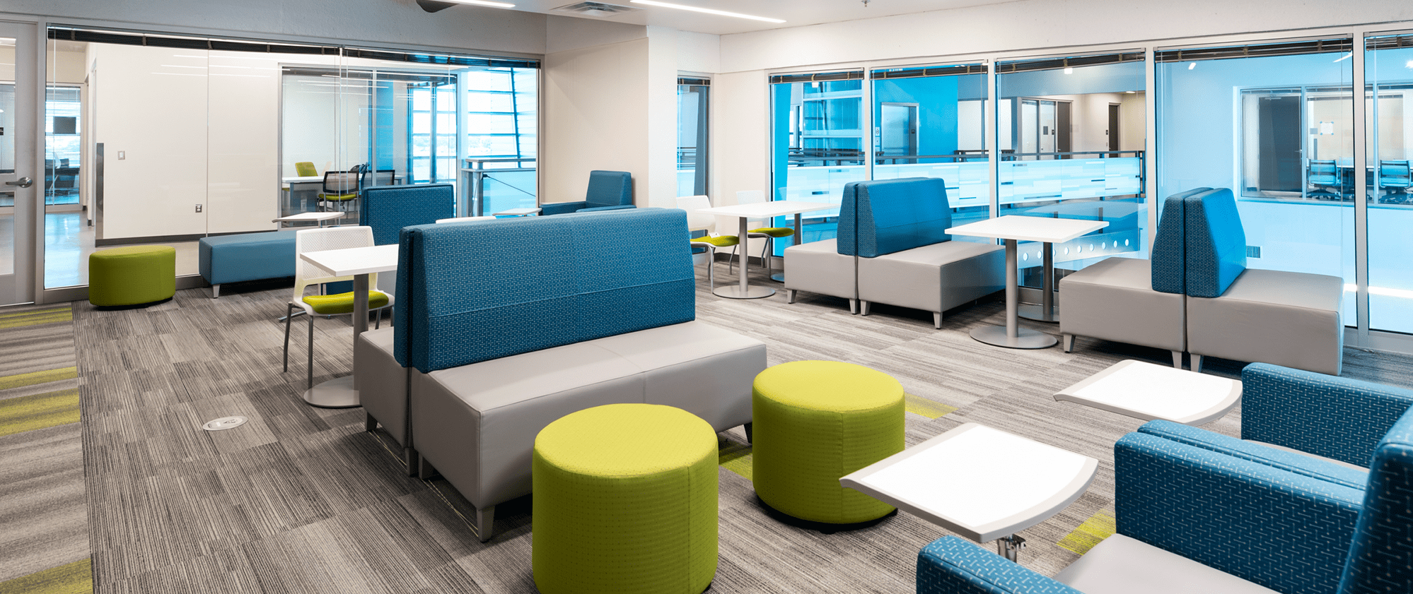 Student lobby with modern seating including tables, chairs and individual work stations.