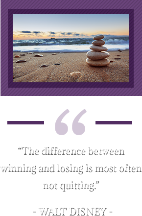 """The difference between winning and losing is most often not quitting."" – Walt Disney. Pebbles and sand on beach."