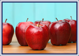 Apples sit on a wooden surface