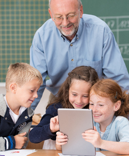three students and a teacher looking at a tablet