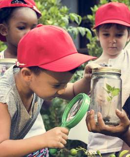 students wearing red hats using a magnify glass to look in a jar
