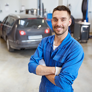 Car mechanic poses in a garage