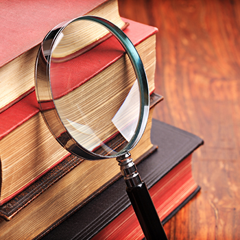 Magnifying glass leans against a stack of books