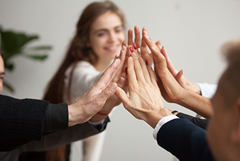 Business woman giving a high five to team members