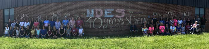 Staff in front of brick wall with NDES 40 Years Strong written on it