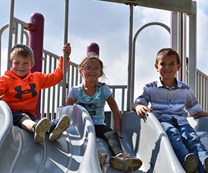 Three students sitting on a slide