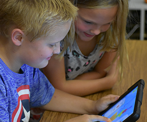 A boy and a girl use a computer tablet