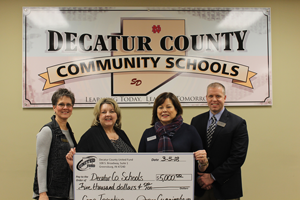 Decatur County Community Schools. Staff holds check for 5,000 from United Funds made out to Decatur County Schools.