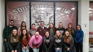 Students pose in front of a South Decatur sign with the cougar logo on it