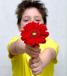 Male student holding up a flower