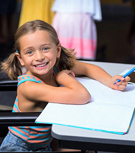 Smiling female student holds a colored pencil on top of a notebook