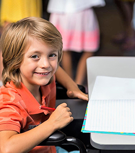 Smiling male student holds a colored pencil near a notebook